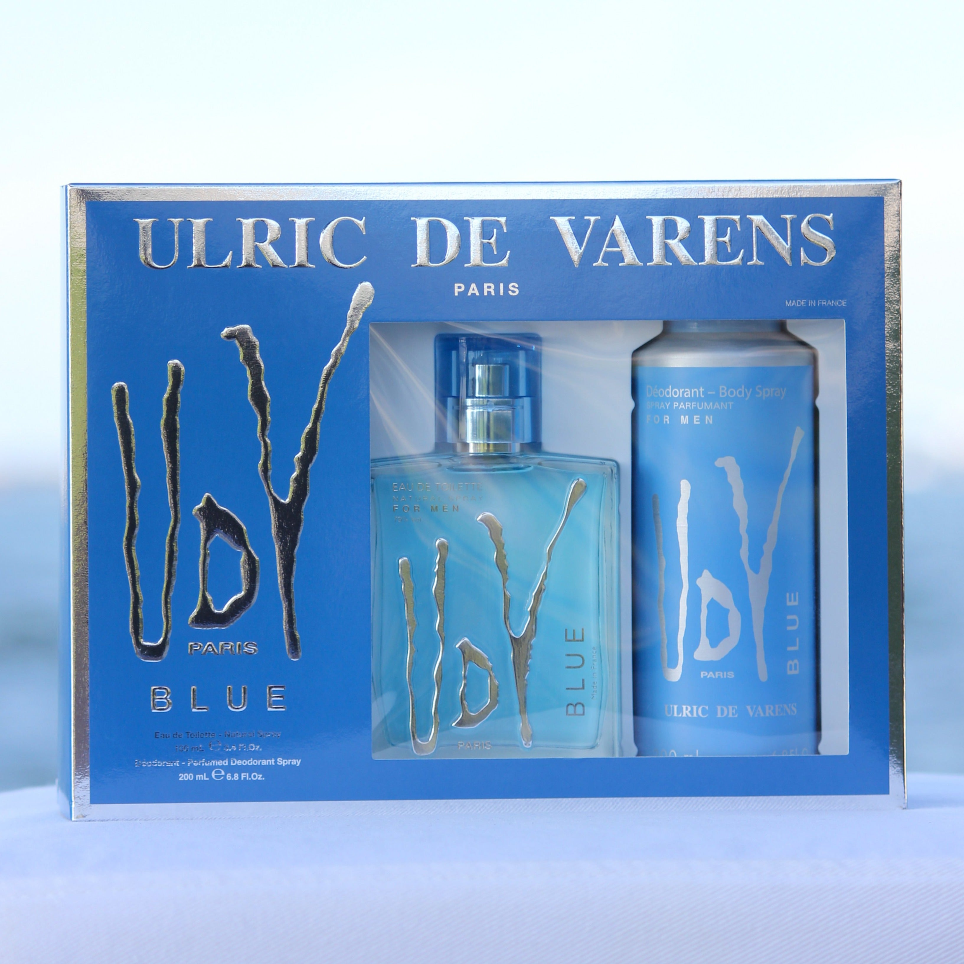 Ulric De Varens UDV Blue Gift Set men's perfume 3.4 EDT and deodorant 6.8 oz in front of beach