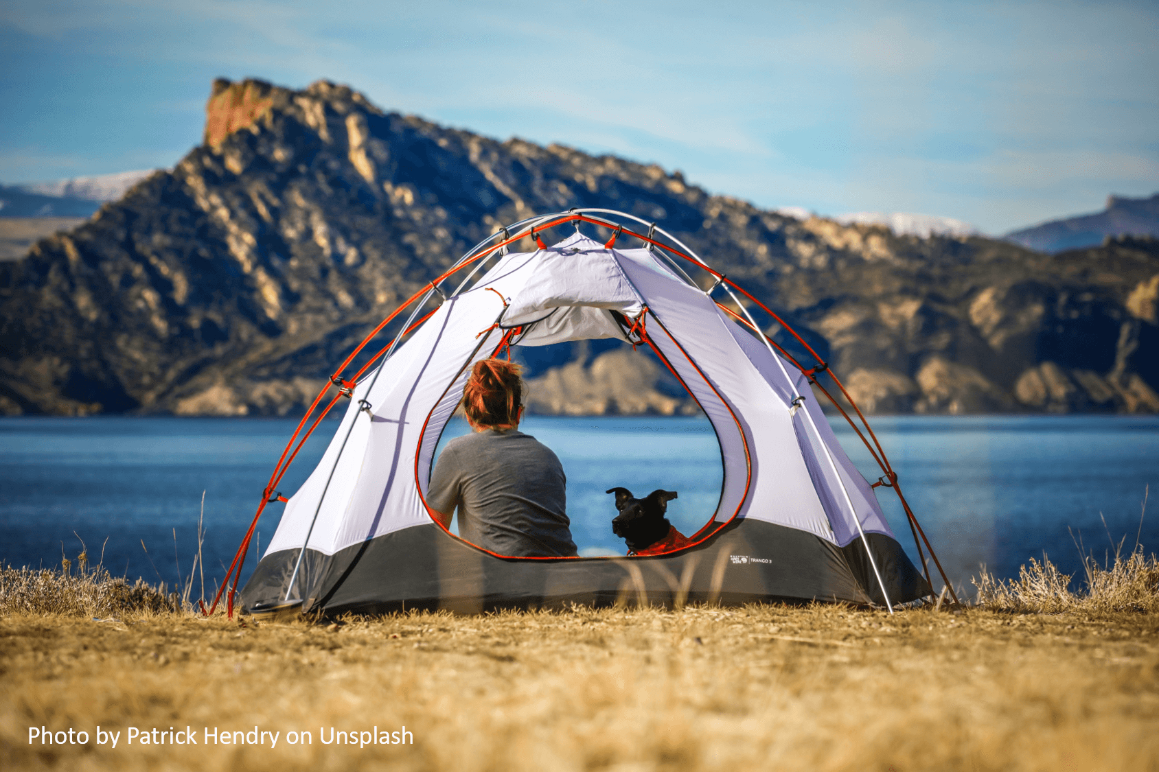 woman in a tent with a dog by a lake