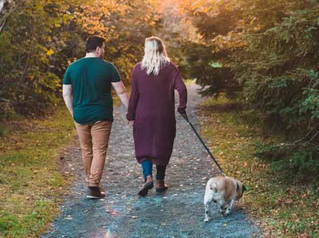 couple walking on trail with small dog on a leash