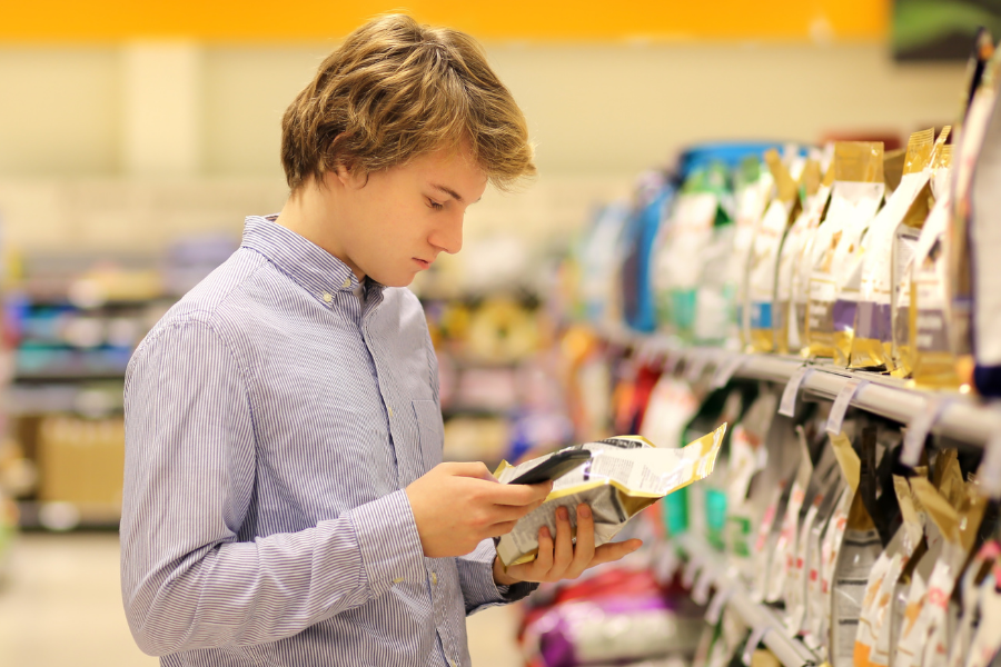 gen z blonde man standing in pet food aisle looking at pet food lablel and checking his phone