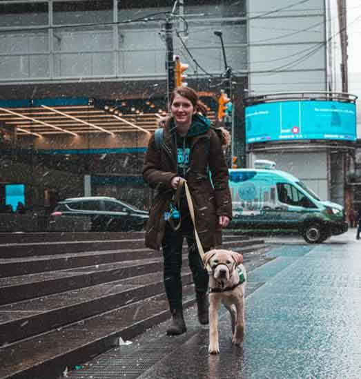 woman walking dog in city on snowy day