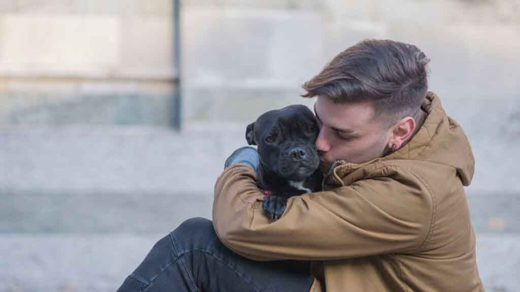 man in tan jacket snuggling with black pug
