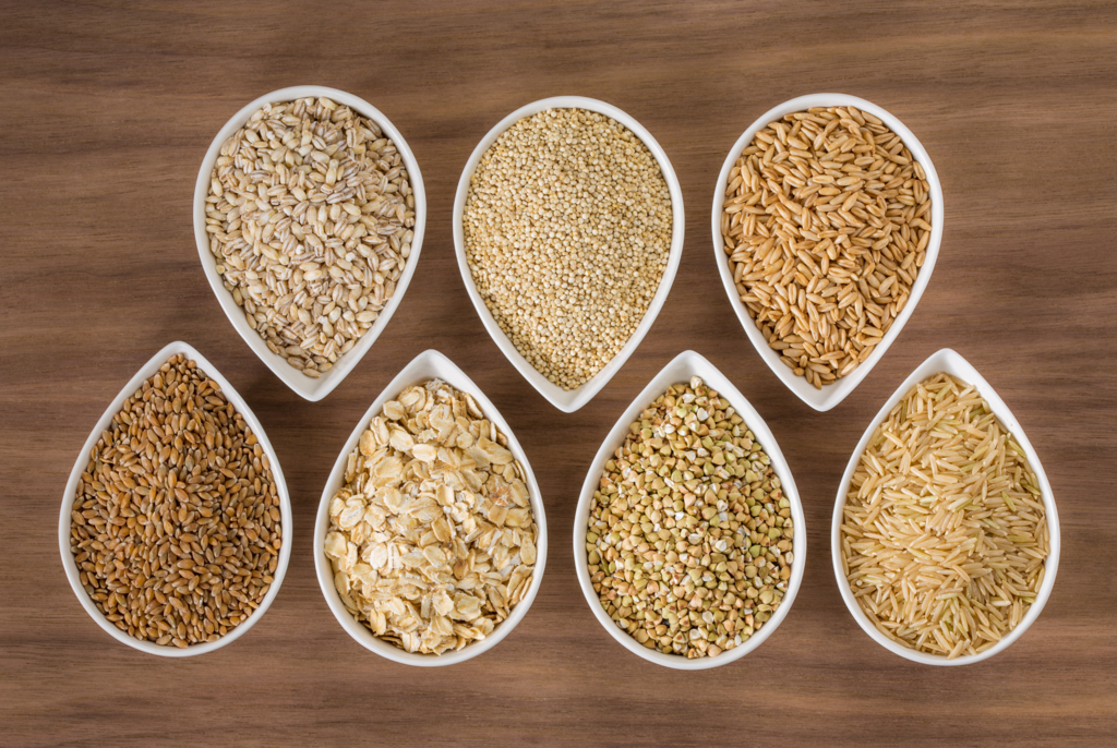 variety of grains in tear drop white bowls on a wood table