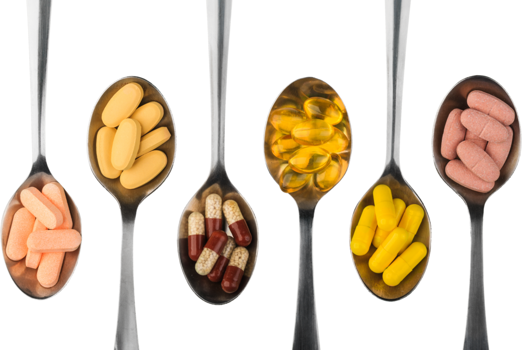variety of vitamins and minerals on spoons on a white background