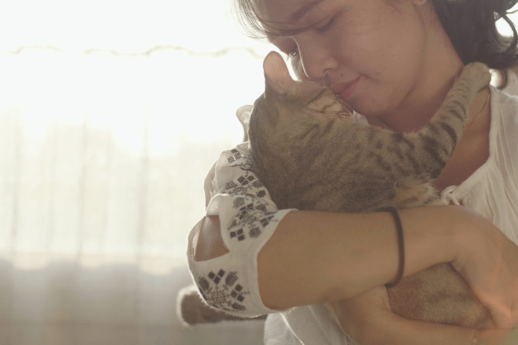 woman holding cat close to face