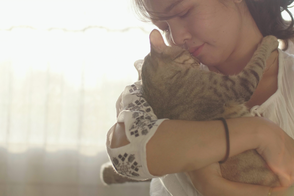 young woman snuggling with a gray tabby cat in her arms