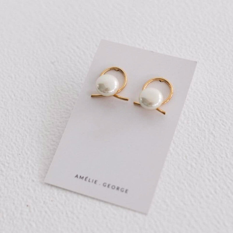 White earring card with a pair of Amelie George Airlie earrings. They have A beige pearl sits in front of a gold ribbon handtwisted into a knot for modern bridal looks