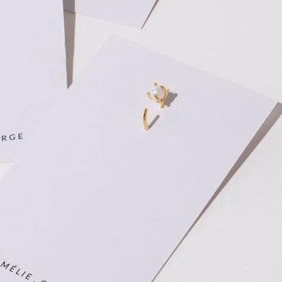 White earring card display with Amelie George Bridal ARIA mini gold earrings with pearl set in a claw for brides stacking earrings in c cuff.