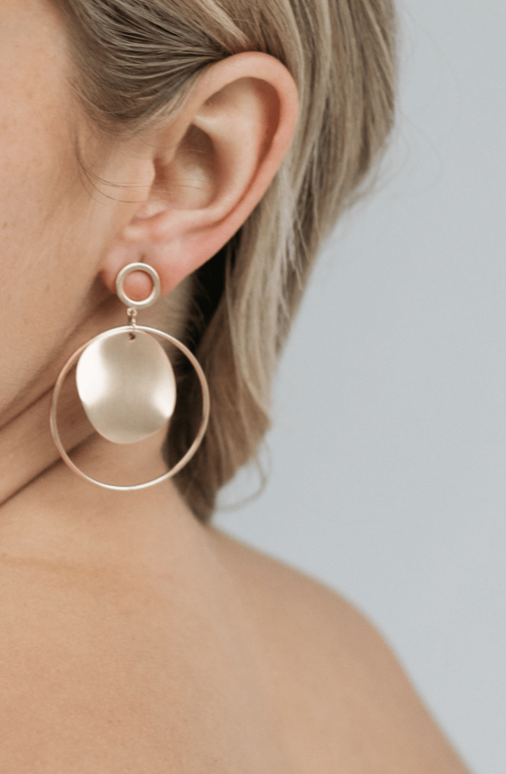 Close up of ear with blonde bride wearing Statement wedding earrings for a bold, fun bridal look with delicate hoops adorning our signature brushed gold disc.
