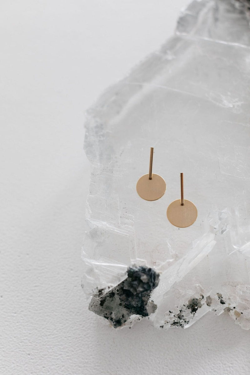 Crystal with flatlay of Amelie George Bridal's signature brushed gold disc is set on a drop bar allowing movement on these wedding earrings.