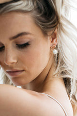 A model wears Airlie earrings which have A beige pearl sits in front of a gold ribbon handtwisted into a knot for modern bridal looks. The model is lifting her blonde hair