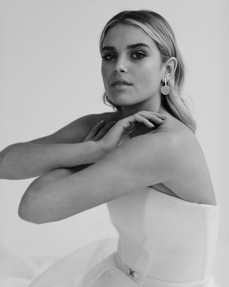 Black and white photography of bride wearing Karen Willis Holmes Strapless dress with arms crossed in front wearing Amelie George Bridal's signature brushed gold disc is set on a drop bar allowing movement on these wedding earrings.