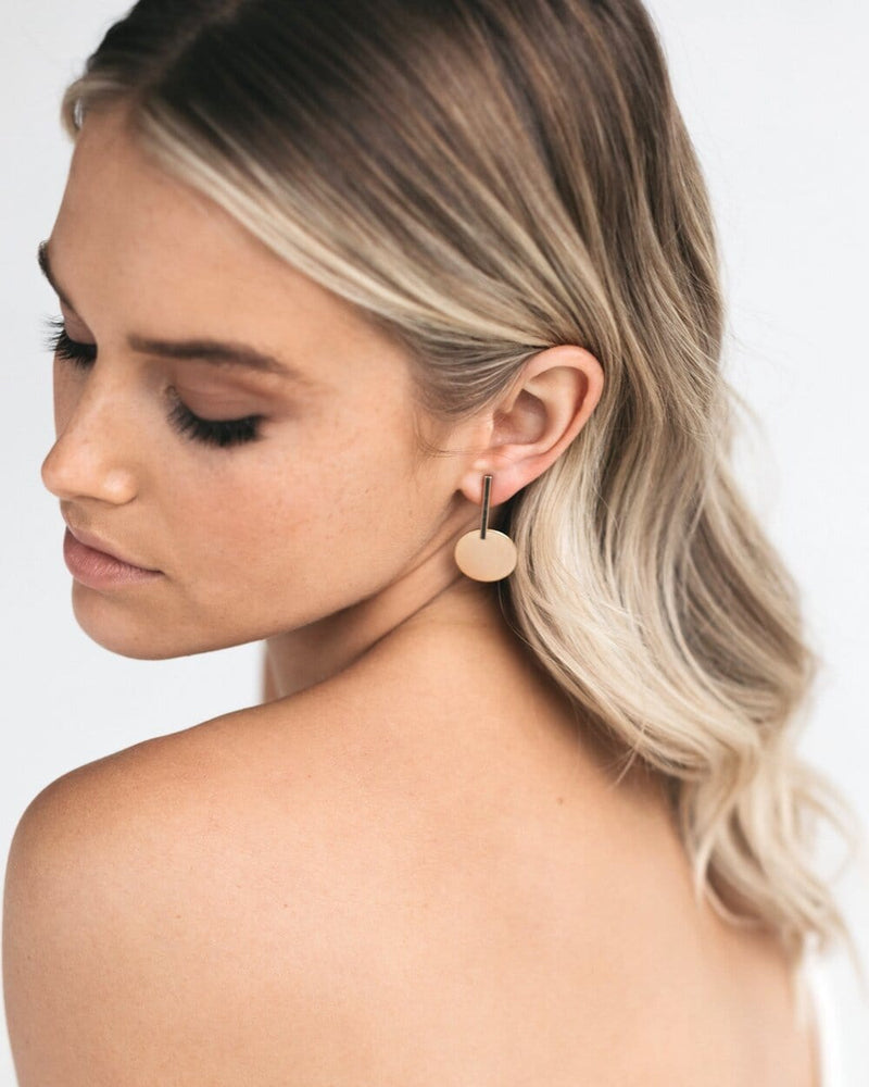 Bride with natural wedding eye makeup wearing Amelie George Bridal's signature brushed gold disc is set on a drop bar allowing movement on these wedding earrings.