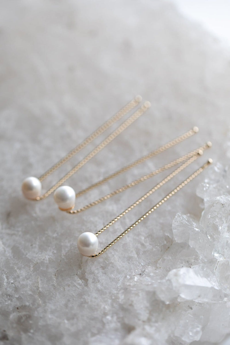 3 natural freshwater pearl hairpins on 18k gold hairstylist pins are sitting on a beautiful white crystal