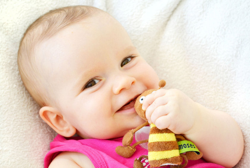 smiling baby chewing on toy