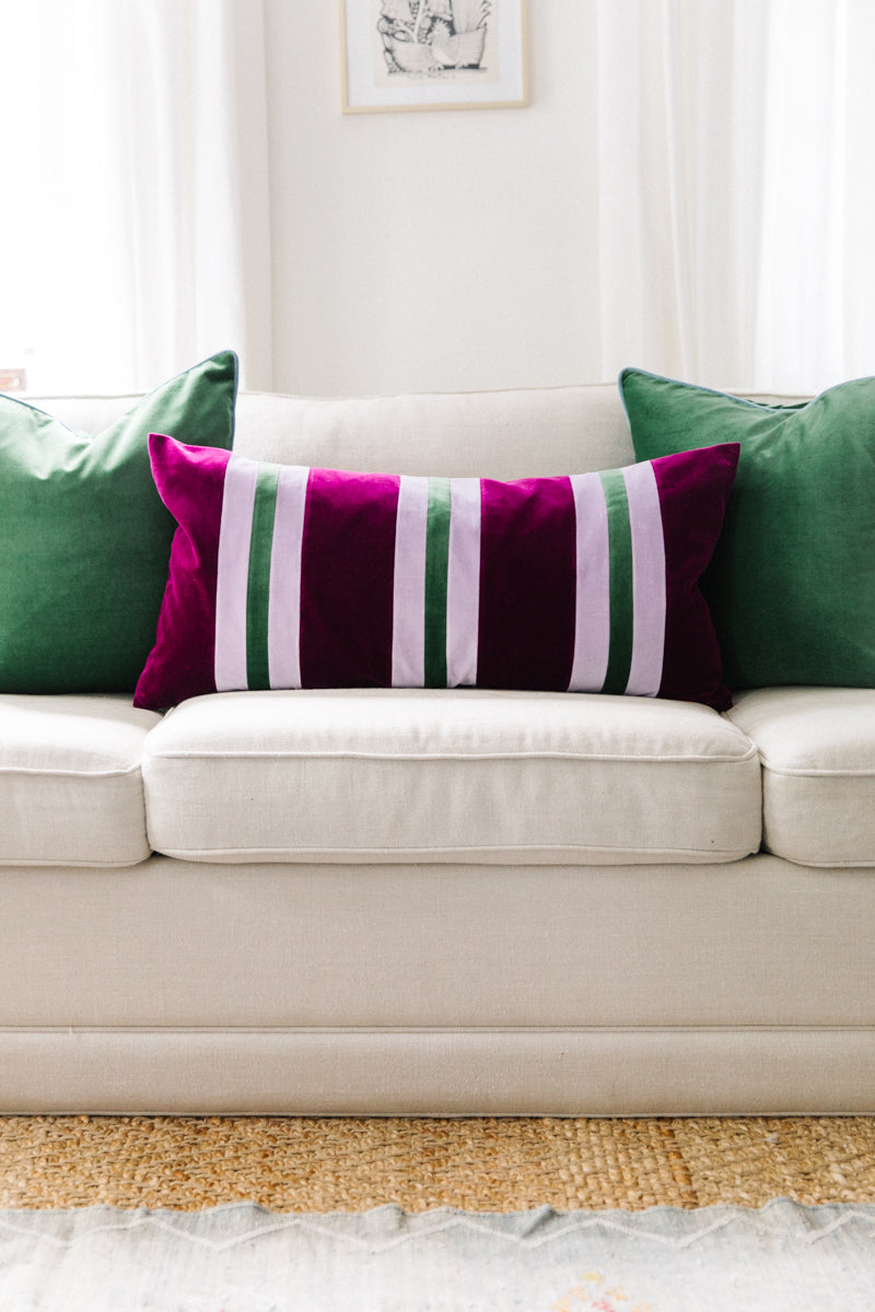 Furbish Studio - Gianna Striped Velvet Lumbar Pillow in Mulberry, Grass Green and Lavender styled on white couch with deep green throw pillows