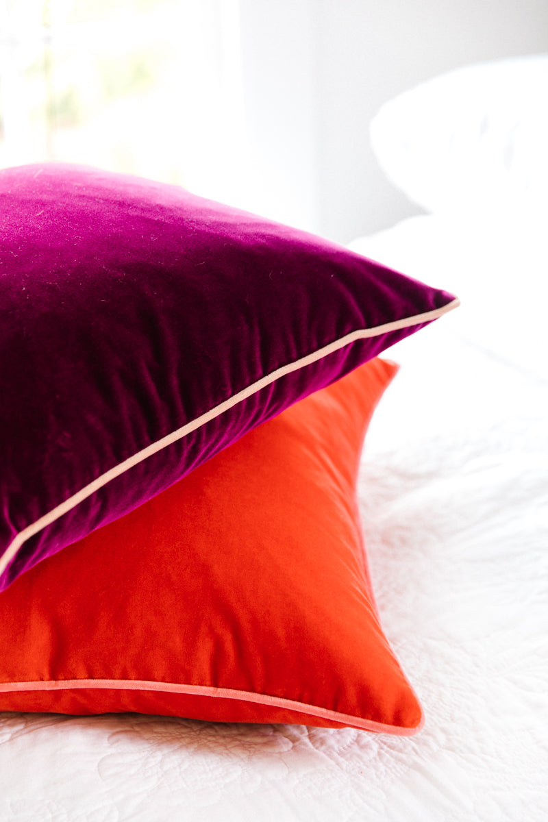 Furbishs Studio - Chloe Velvet Pillow in Tomato Red with Pink Piping Trim styled on white bed linens with purple pillow