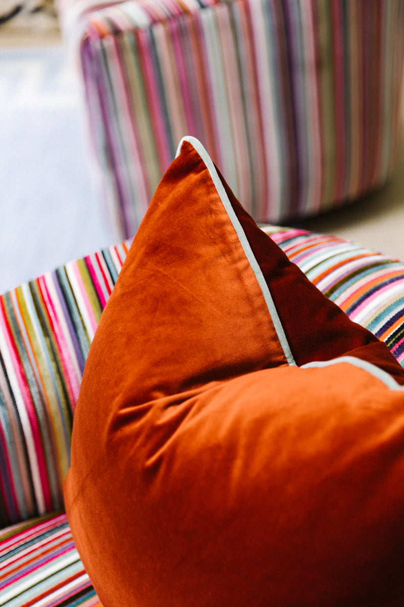 Furbish Studio - Chloe Velvet Pillow in Terra Cotta with Mint Green Piping styled on striped club chair