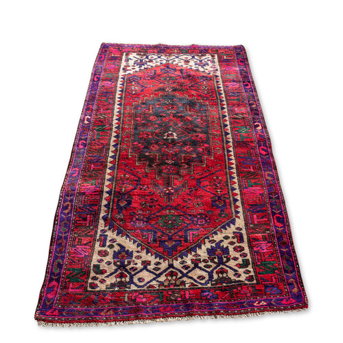 Vintage turkish rug in vibrant red, pink, purple, green, and creme.  3.9' wide by 7.6' long.