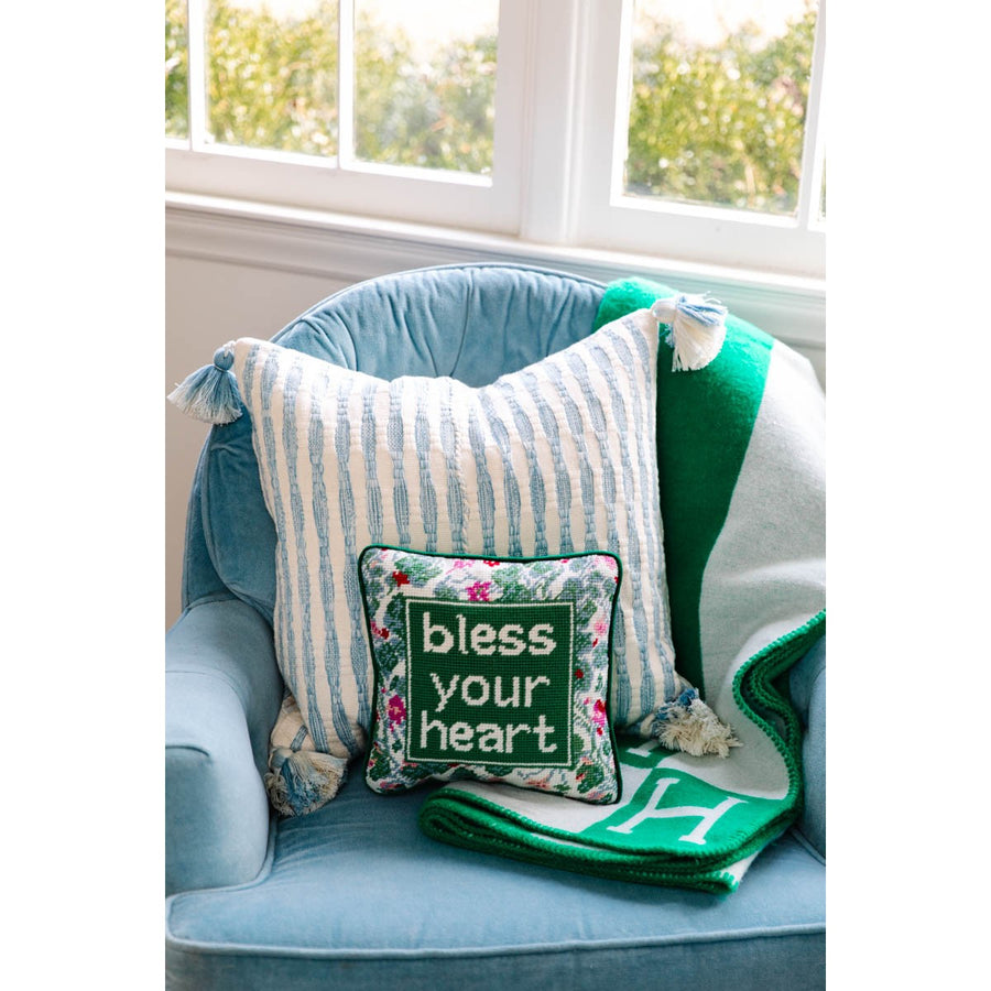 Furbish Studio - Bless Your Heart Needlepoint Pillow styled on blue club chair with striped pillow and green throw blanket