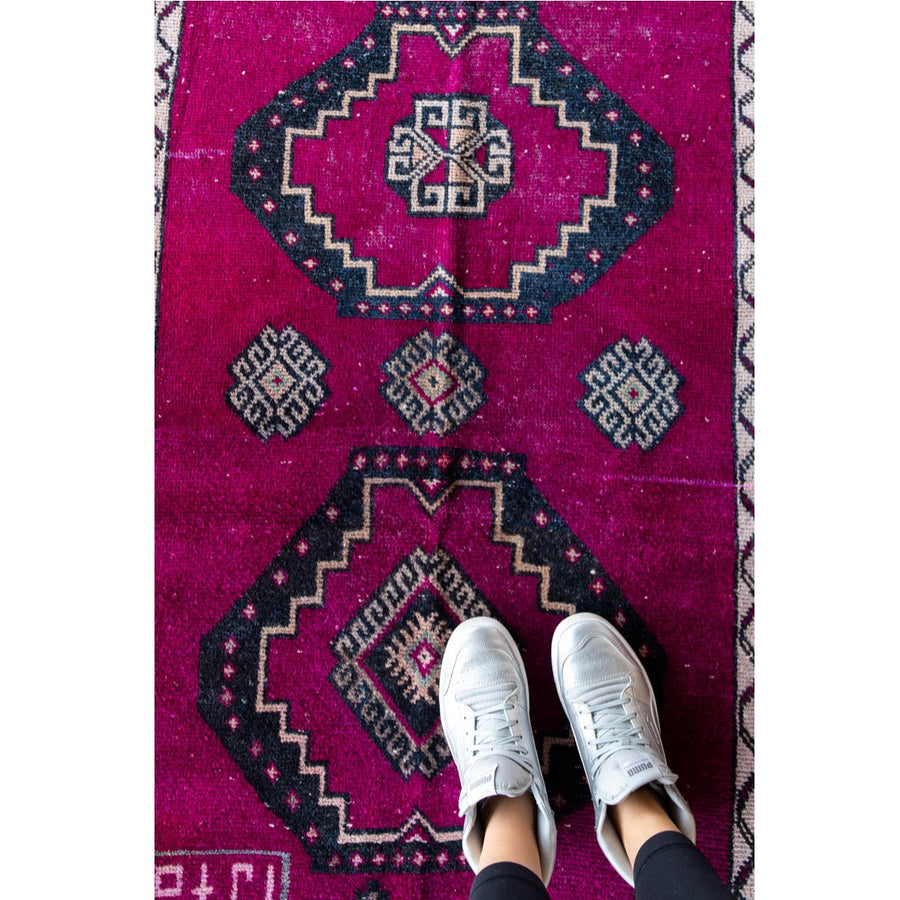 Furbish Studio - Papaya vintage rug with person wearing tennis shoes standing on it