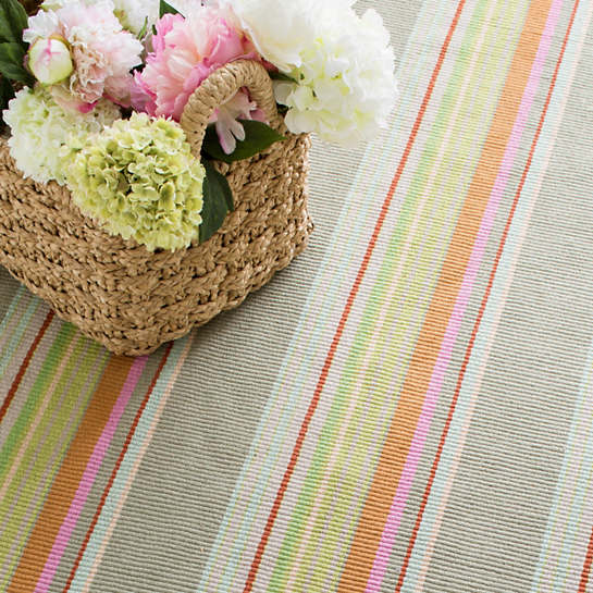 Furbish Studio - Marina Cay Striped Indoor/Outdoor Rug in soft sage, taupe, aqua, and orange styled with a basket of peonies and hydrangea