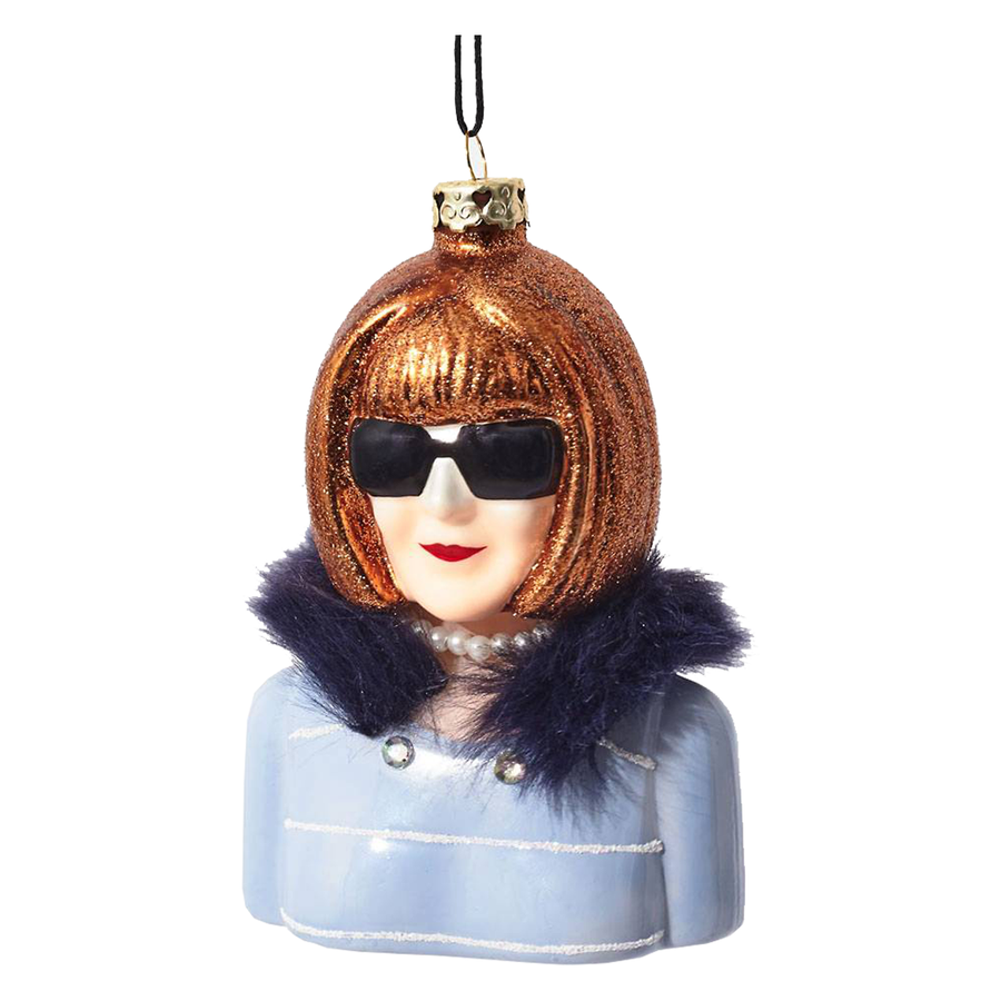 Editor of Vogue, Anna Wintour Christmas tree ornament.  Anna Wintour is wearing a blue tweed jacket with black fur collar and her signature big black sunglasses.