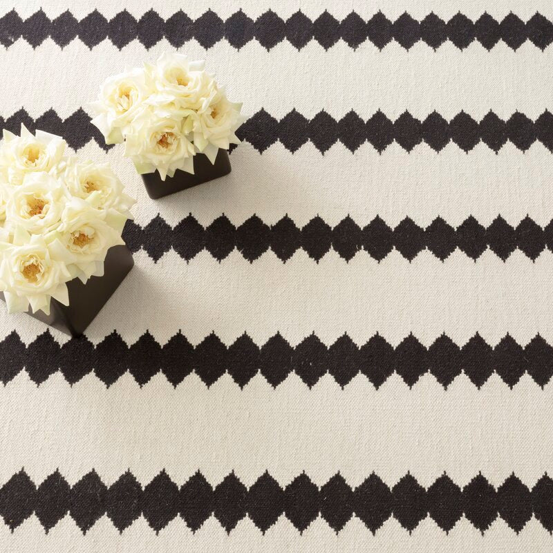 Furbish Studio - Palo Santo Dhurrie Rug - Ivory/Black close up with white roses