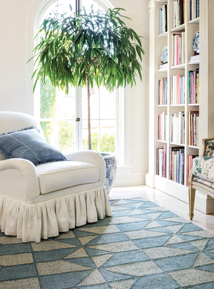 Furbish Studio - Highlands Rug blue loom knotted cotton rug shown in library with white easy club chair