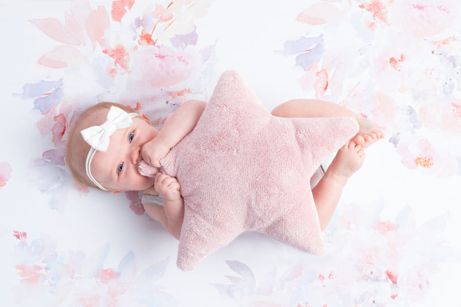 baby laying on blanket holding star pillow