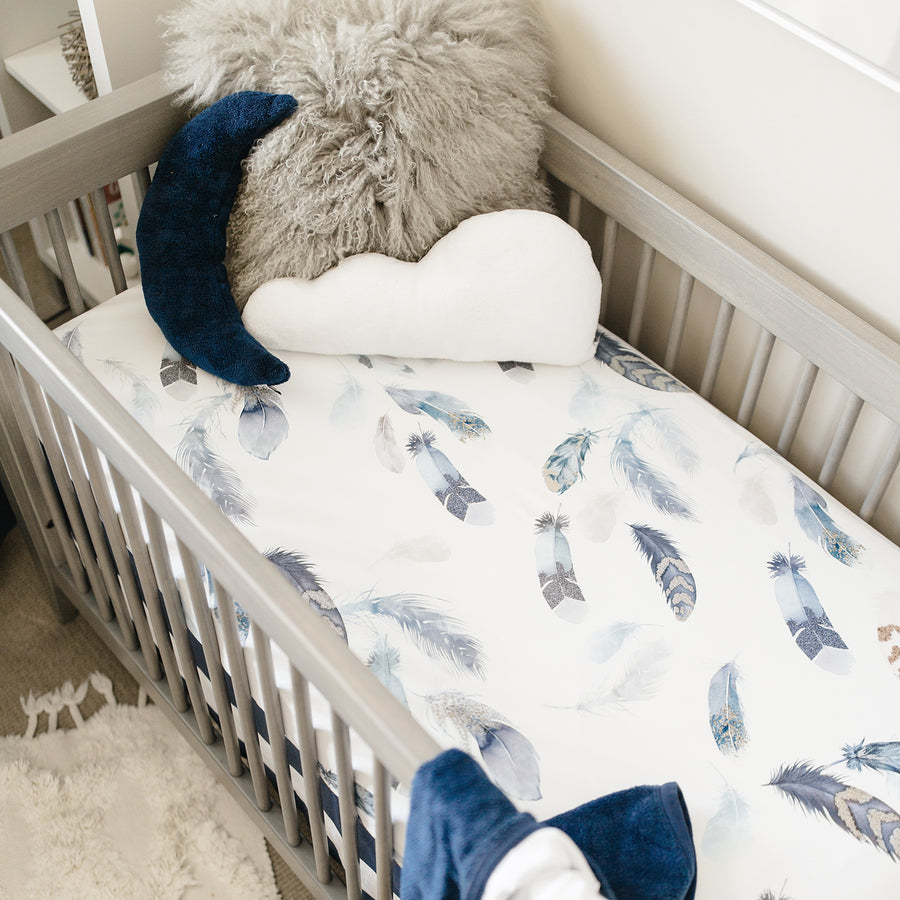 crib with feather crib sheet on it