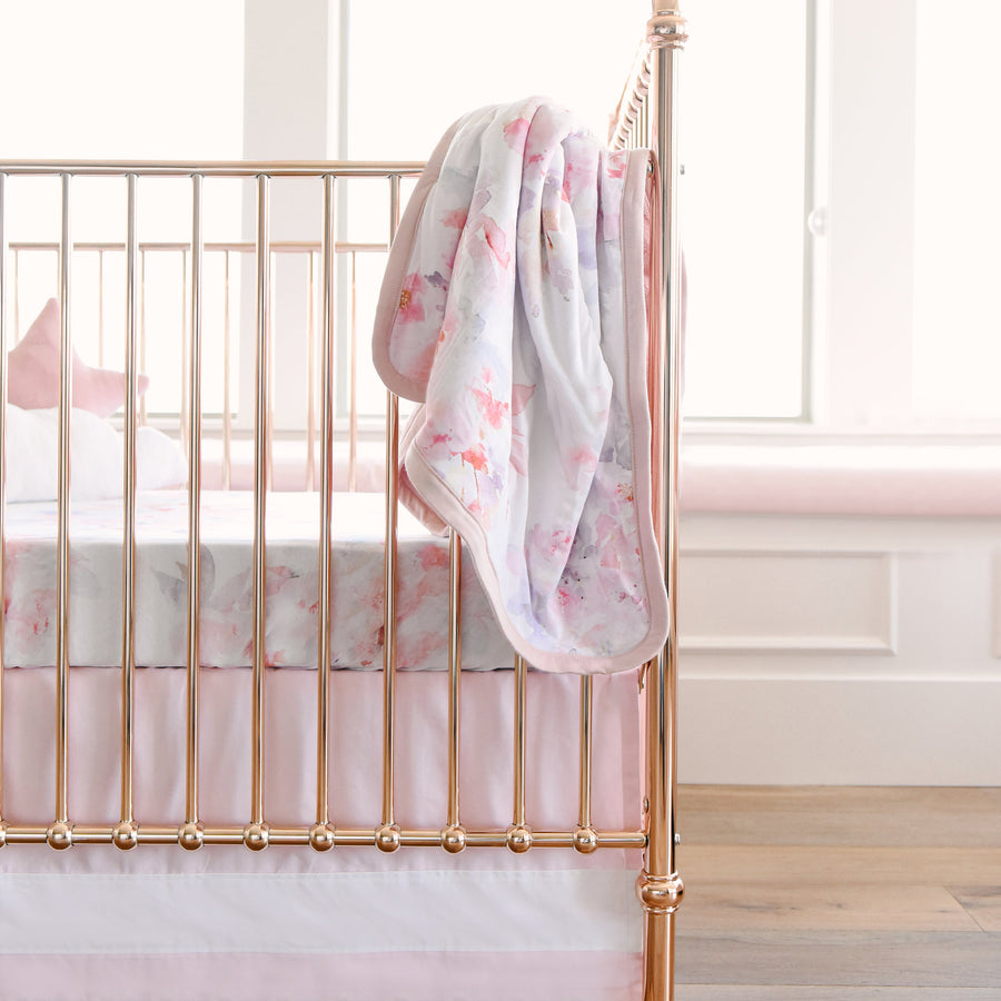 crib with floral blanket hanging on the side