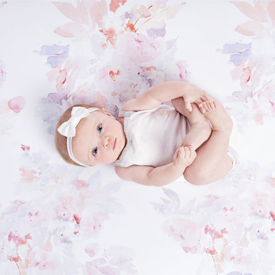 baby laying on floral crib sheet