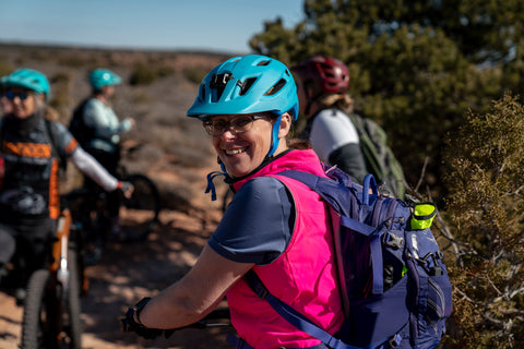 Jen Hoge, Chapter Leader for SLC, wears a bright pink vest and fully stocked backpack while mountain biking in Moab, UT.