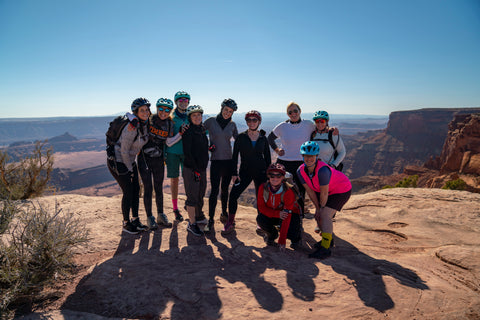 A group of women of all ages during a mountain biking trip, overlooking Moab, UT with arms outstretched and smiles on their faces!