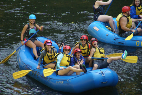 A group of women in a raft with pfd's and paddles having a great time!
