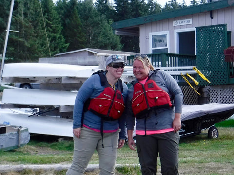 Two women wearing red PDFs smile as they learn about their kayaks before setting off on an adventure!