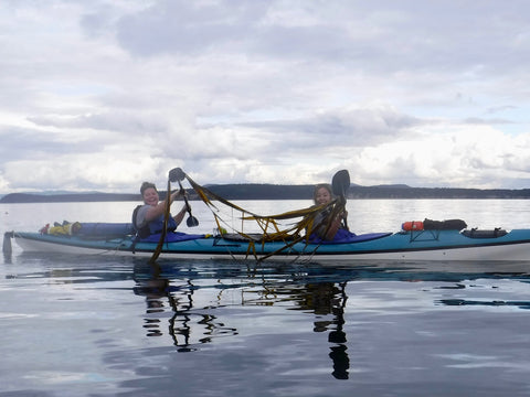 Two smiling women in a tandem kayak use their paddles to hold up giant pieces of seaweed!