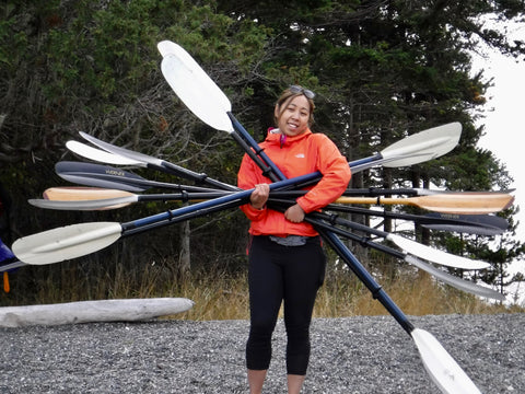 A smiling women holds a lOT of kayak paddles!