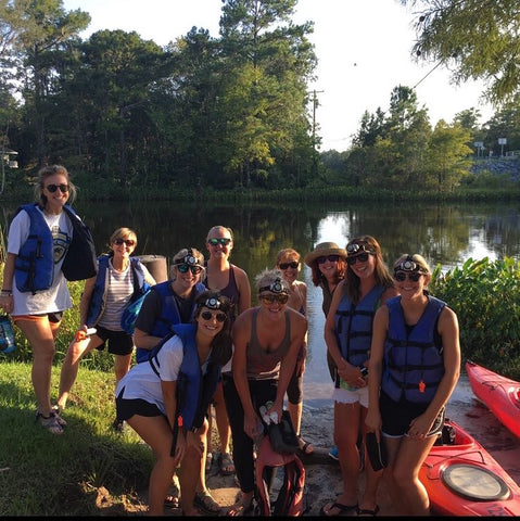 A smiling group of women beside Wakulla river with their kayaks and headlamps on!