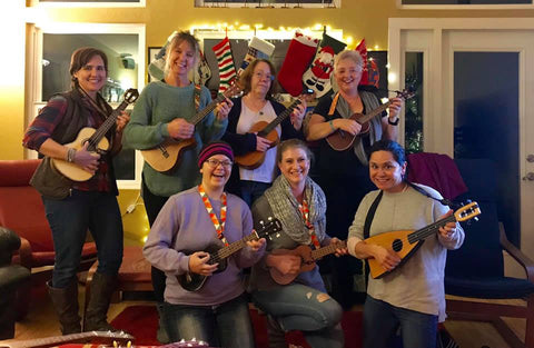 A group of smiling women proudly holding their ukuleles.
