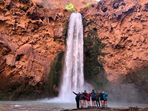 A group of women at the bottom of a 200 foot waterfall looking happy and triumphant!