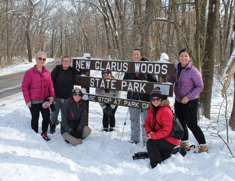A group of women around a State Park sign during a winter snow hike!