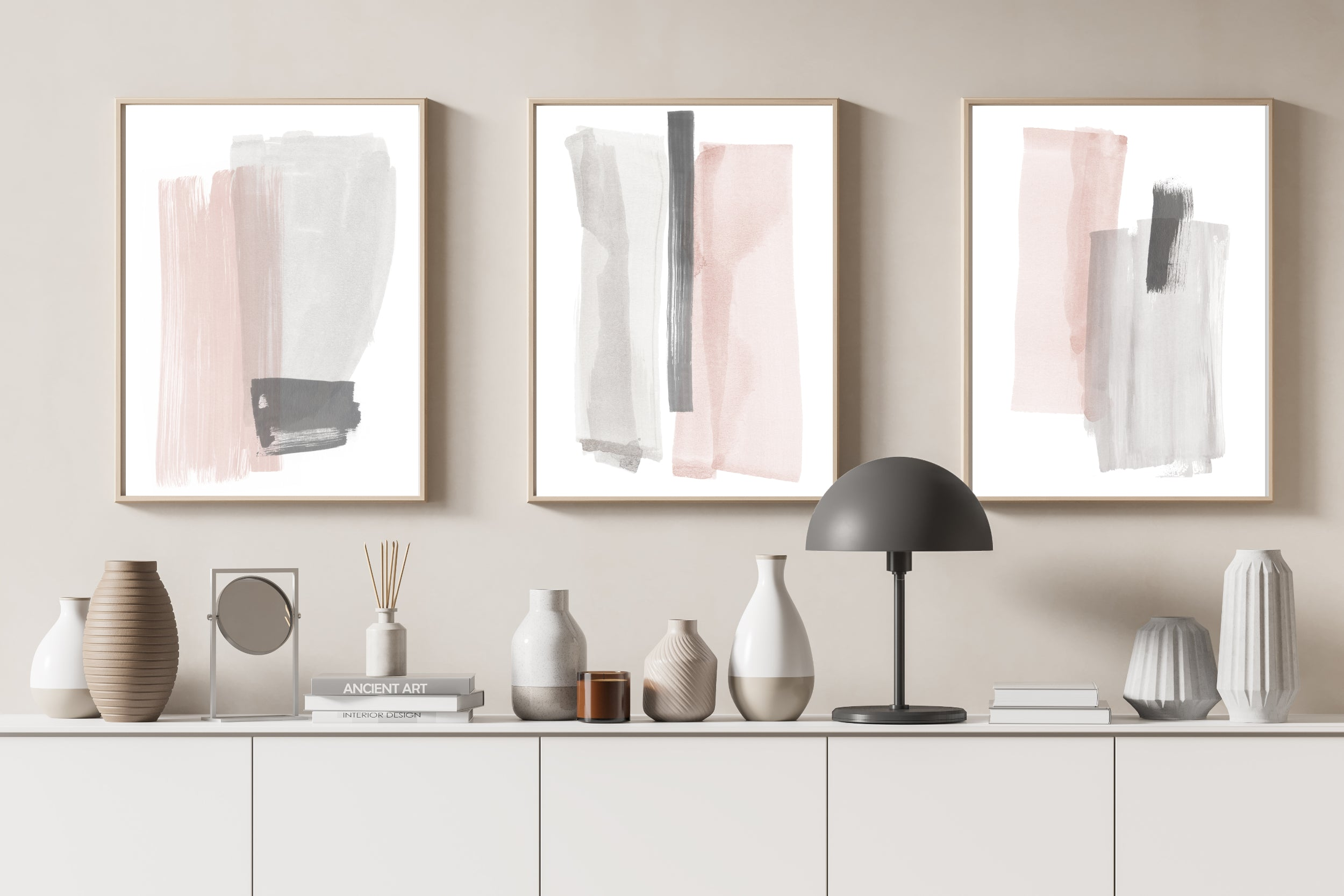 Set of three abstract prints in pink and grey against a neutral taupe background