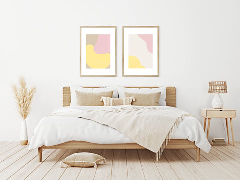 Set of Two Abstract Pastel Art Prints in Pinks, Yellows and Light Brown Neopolitan Colours in a Bedroom Setting with Bed, Bedside Table and Dried Grasses