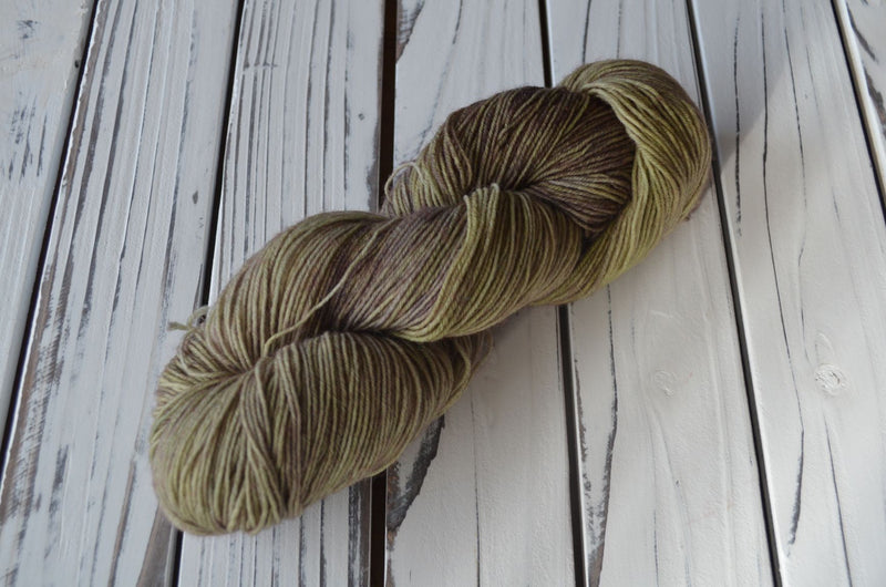 A skein of sock yarn in a light greyish yellow with a hint of a purple halo on top. 75% wool 25% sock yarn 100 grams 3.5 oz 420 metres 466 yards