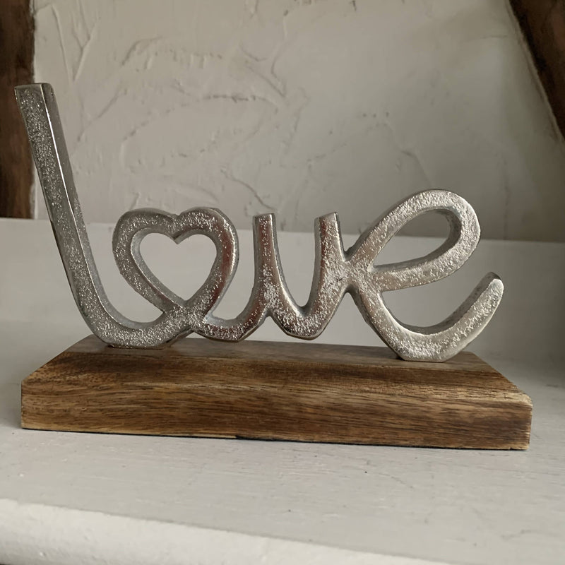 "Silver metal ""love"" on a wooden stand"