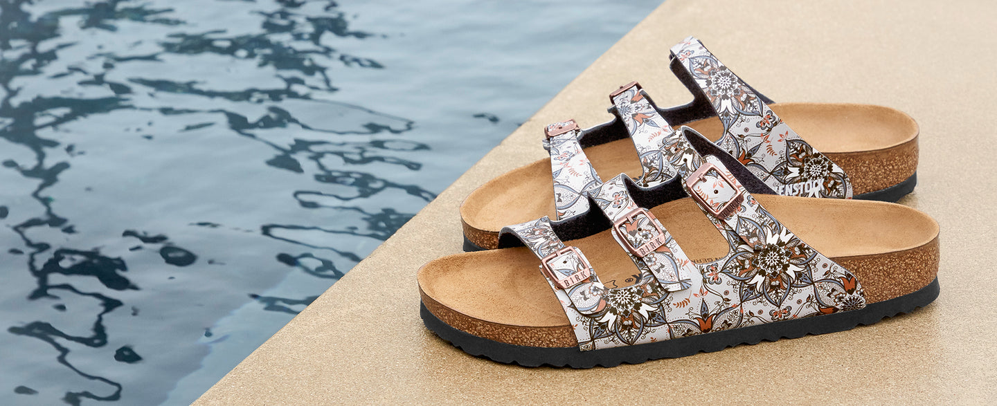 Floral print Birkenstock sandals next to a pool