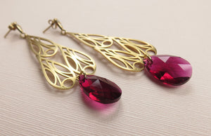 A close up picture of gold Art Deco inspired chandelier earrings resting on a textured pink paper.