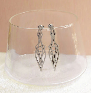 Art deco dagger stud earrings. Made of brushed sterling silver and oxidized for contrast. Hanging on a glass.